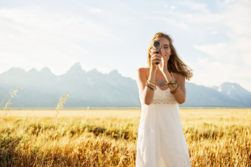 Hispanic woman in white dress using video camera in tall grass