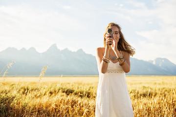 Hispanic woman in white dress using video camera in tall grass