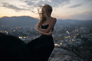 Caucasian woman on hilltop near cityscape view