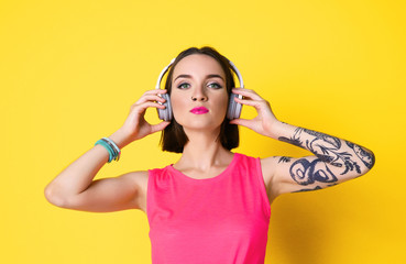 Beautiful young woman with tattoo wearing headphones and posing on yellow background