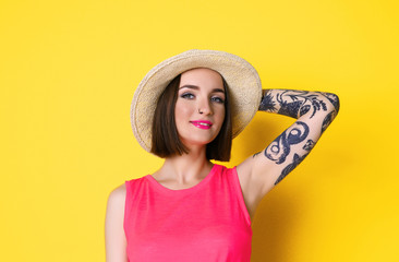 Beautiful young woman with tattoo wearing hat and posing on yellow background
