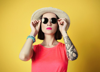 Beautiful young woman with tattoo and sunglasses wearing hat on yellow background