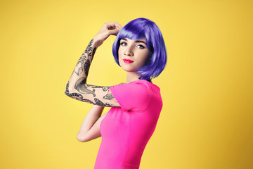 Beautiful young woman with tattoo wearing blue wig and posing on yellow background