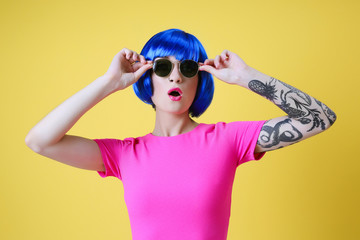 Beautiful young woman with tattoo wearing blue wig and sunglasses on yellow background
