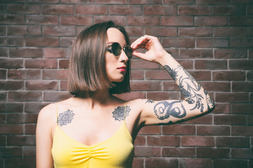 Beautiful young woman with tattoo wearing sunglasses and posing on brick wall background