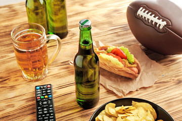 Beer bottles, ball and snack on wooden background