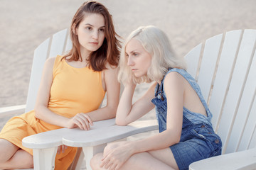 Portrait of two pensive sad white Caucasian unformal young girls hipster students friends outside on beach summer day sitting on chairs silent, best friends forever, selective focus