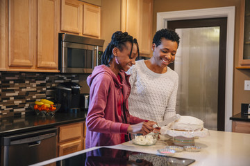Black mother and daughter decorating cake in kitchen