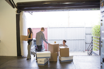 Caucasian business people unpacking boxes in new office