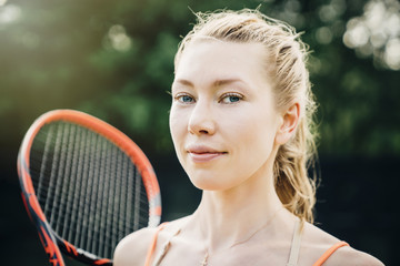 Smiling Caucasian woman holding tennis racket