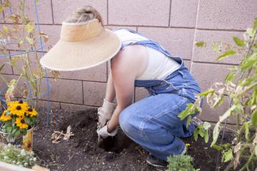 Mixed race farmer digging in garden