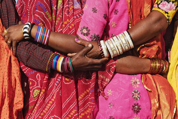 Women in traditional Indian clothing hugging