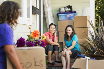 Women moving cardboard boxes into house