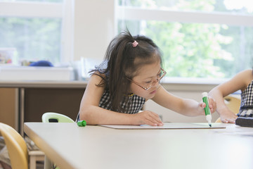 Mixed race Down syndrome students drawing in class
