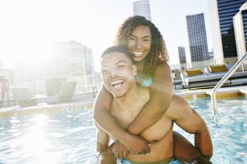 Smiling couple enjoying urban swimming pool
