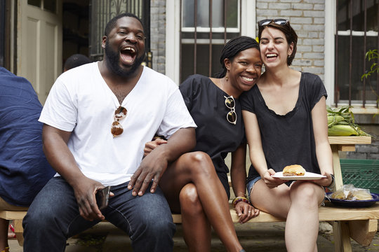Friends laughing at backyard barbecue