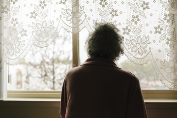 Pensive mixed race older woman looking out window