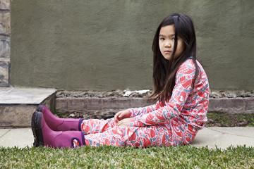 Angry mixed race girl sitting in backyard