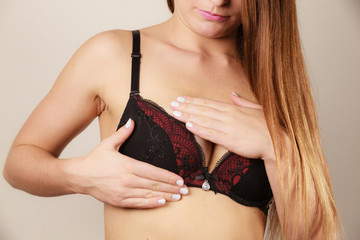 Woman in black bra lingerie taking care of her breasts