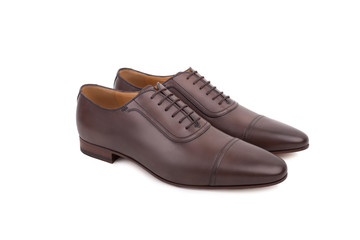 Men's lace-up dress shoes, designed with a slim elongated toe, made from a smooth brown leather. Isolated on a white background.