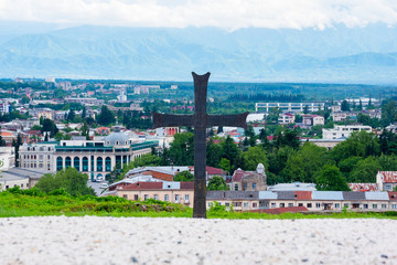 Black metal cross with Kutaisi city panorama in the background, a monument near Bagrati Cathedral, Kutaisi, Georgia. In the center of the cross, Grapevine Cross (Nina's Cross) pictured