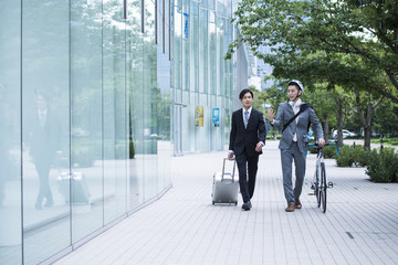 Two businessmen are walking the business district while talking
