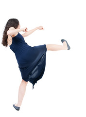 skinny woman funny fights waving his arms and legs. Isolated over white background. The dark curly girl in blue evening dress waving his arms and legs.