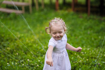 Little girl in white dress plays with sprinkler in the garden