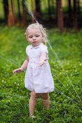 Little girl in white dress plays with sprinkler in the garden