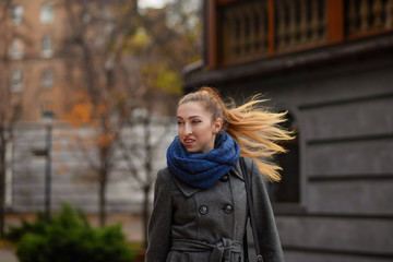 young woman dressed in coat and scarf in the street