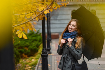 Young woman has a walk in autumn city park
