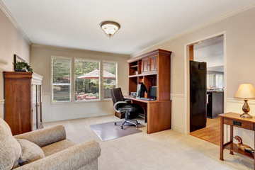 Cozy home office with wooden furniture and carpet floor.
