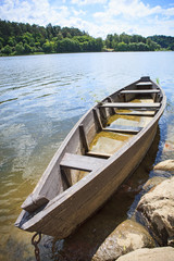 Wooden rowing boat on lake shore