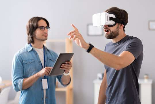 Pleasant colleagues testing virtual reality glasses