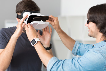 Pleasant cheerful colleagues testing virtual reality glasses