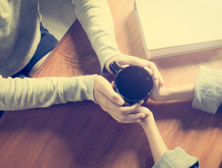 Hands of mother and daughter holding coffee cup