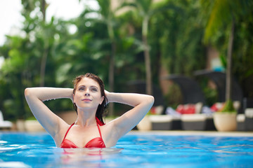 Sensual young woman refreshing in swimming pool