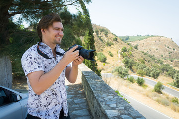 Smiling photographer with professional camera ready for shooting outdoors