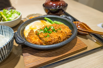 Chicken Fried egg in black dish on wood table