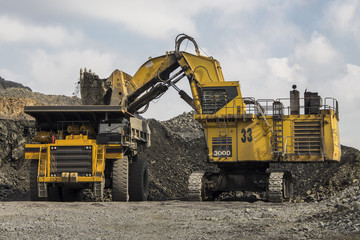 Excavator and truck in the iron quarry