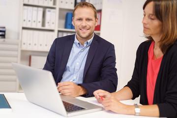 kollegen am arbeitsplatz arbeiten zusammen am laptop