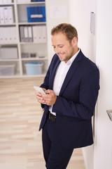 geschäftsmann schaut lächelnd auf sein mobiltelefon