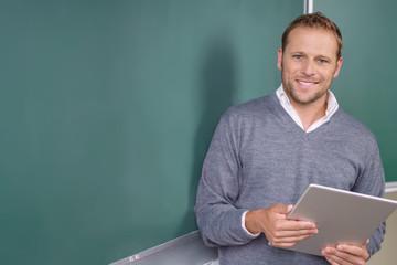 lehrer mit tablet vor der schultafel