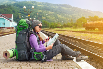 Girl hiker waiting train at the railway station