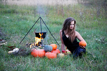 witch with pumpkins in the meadow
