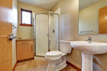 Small bathrom interior with sink, toilet, shower and tile floor.