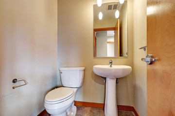 Small bathrom interior with sink, toilet and tile floor.