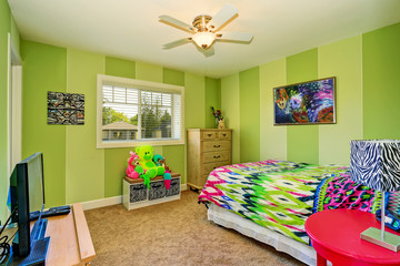 Adorable kids room in green color with bright colorful bedding