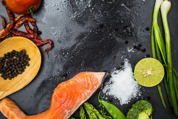 Flat lay of raw salmon fillet and ingredients for cooking on a d