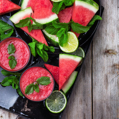 Watermelon slices and drink on a grunge table
